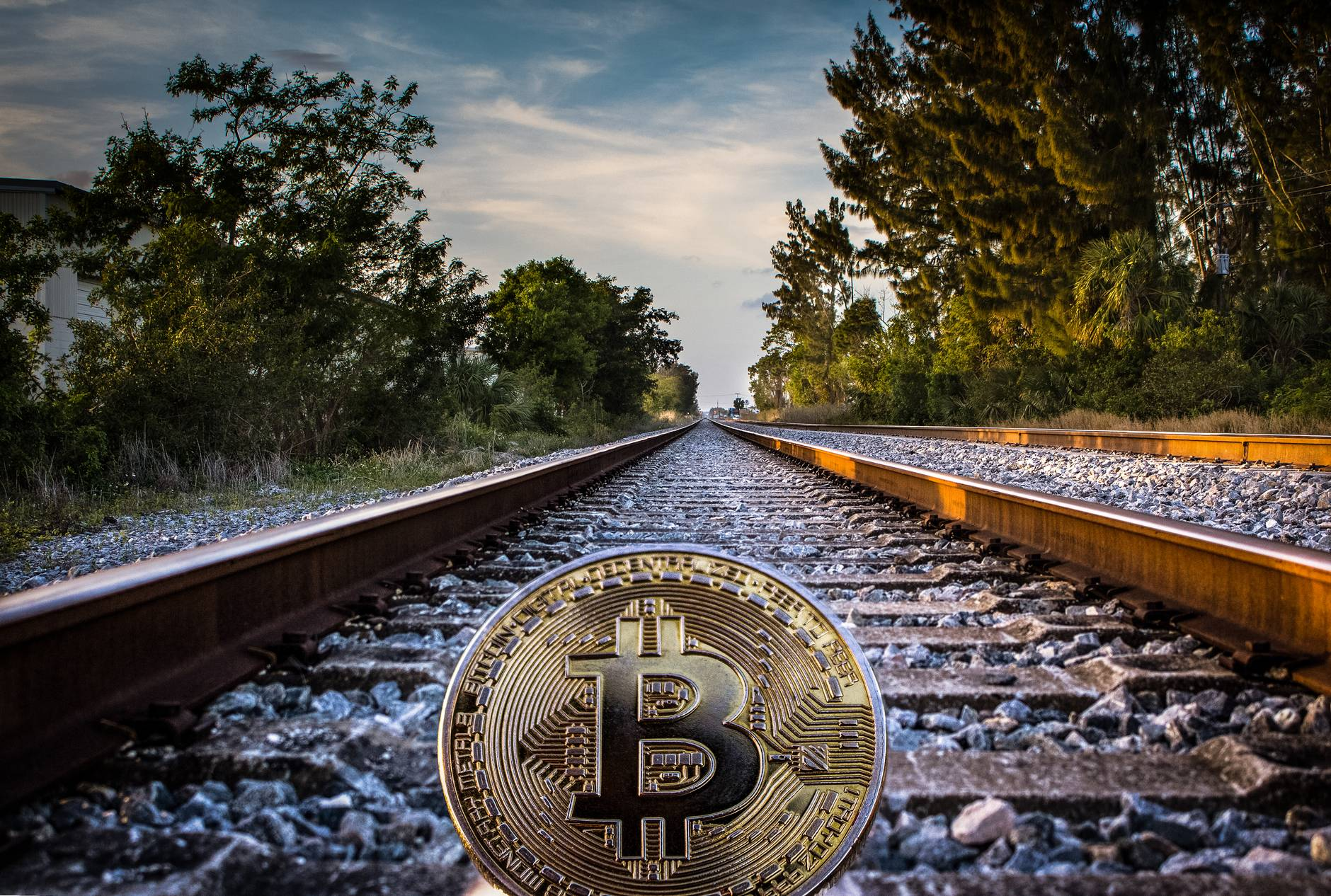 gold colored bitcoin on railroad